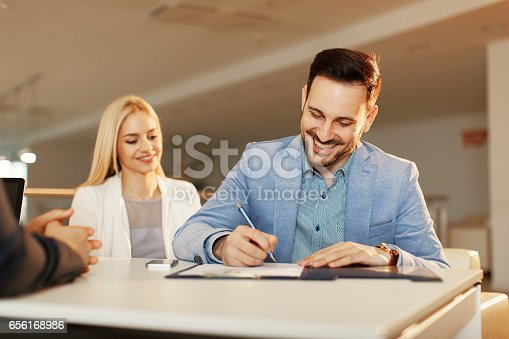 istock Young business couple signing a contract 656168986