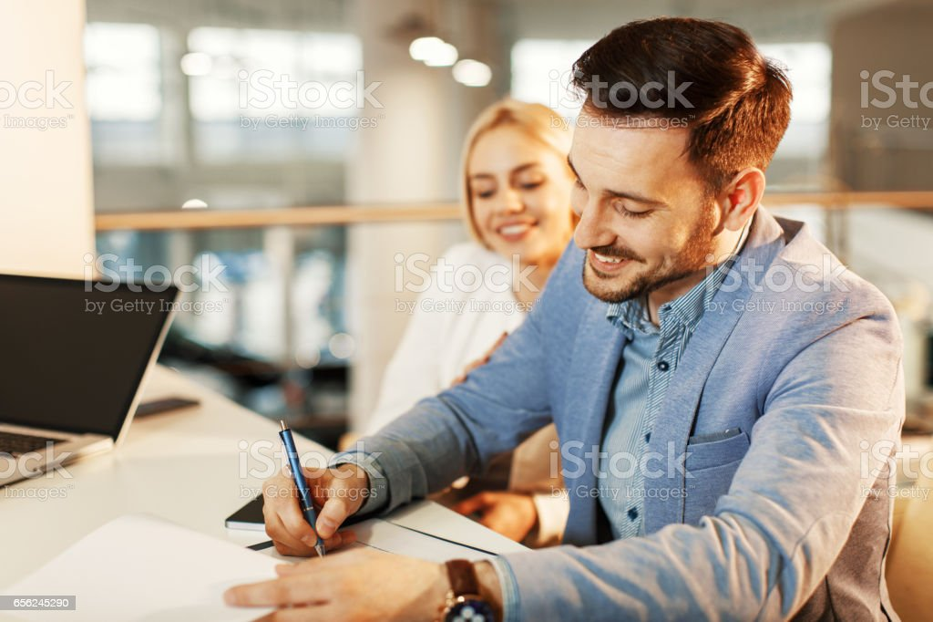 Young business couple signing a contract stock photo