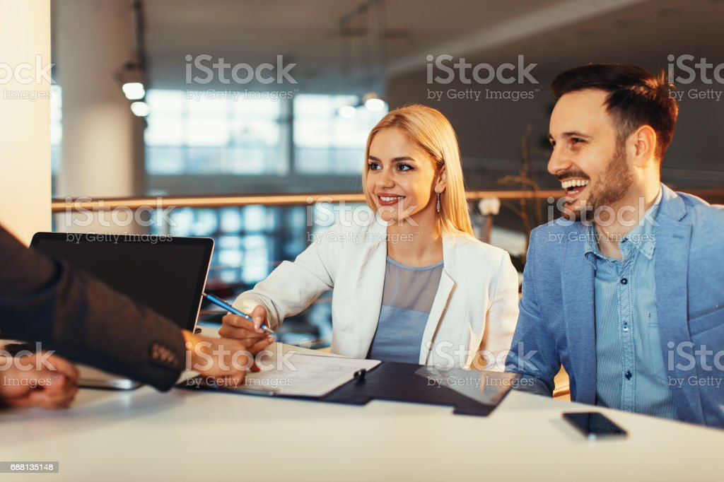 Young business couple signing a contract - Photo