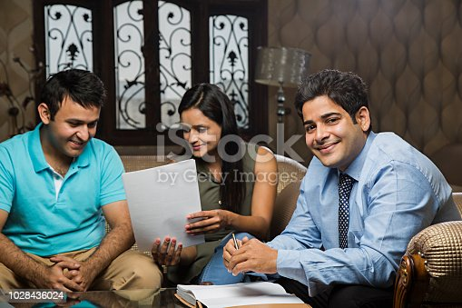 istock Young business couple signing a contract - Stock image 1028436024