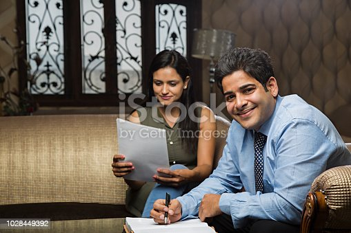 istock Young business couple signing a contract - Stock image 1028449392
