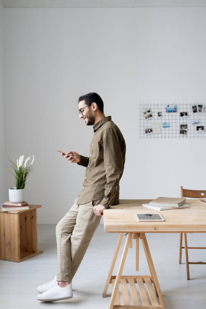 Young business employee in casualwear scrolling in smartphone by workplace stock photo
