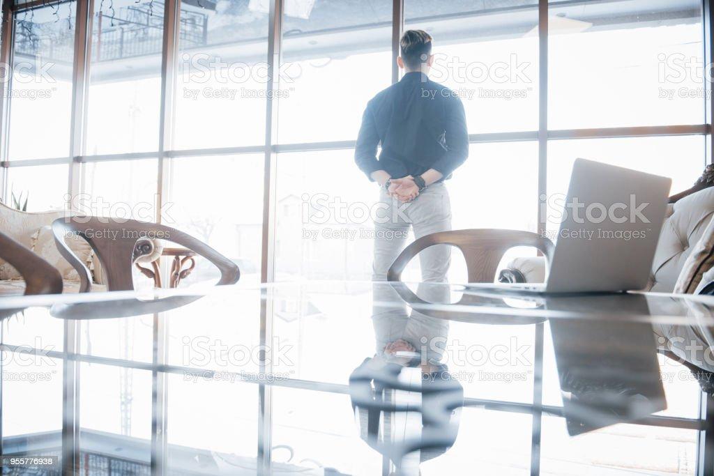 Junger Geschäftsmann und Führer stehen selbstbewusst, in der das Dachgeschoss Büro, Blick auf die Stadt durch die großen Fenster – Foto