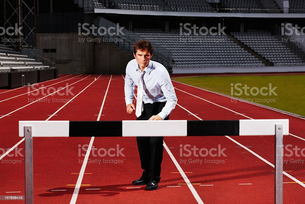 Young business executive getting ready for hurdle race stock photo