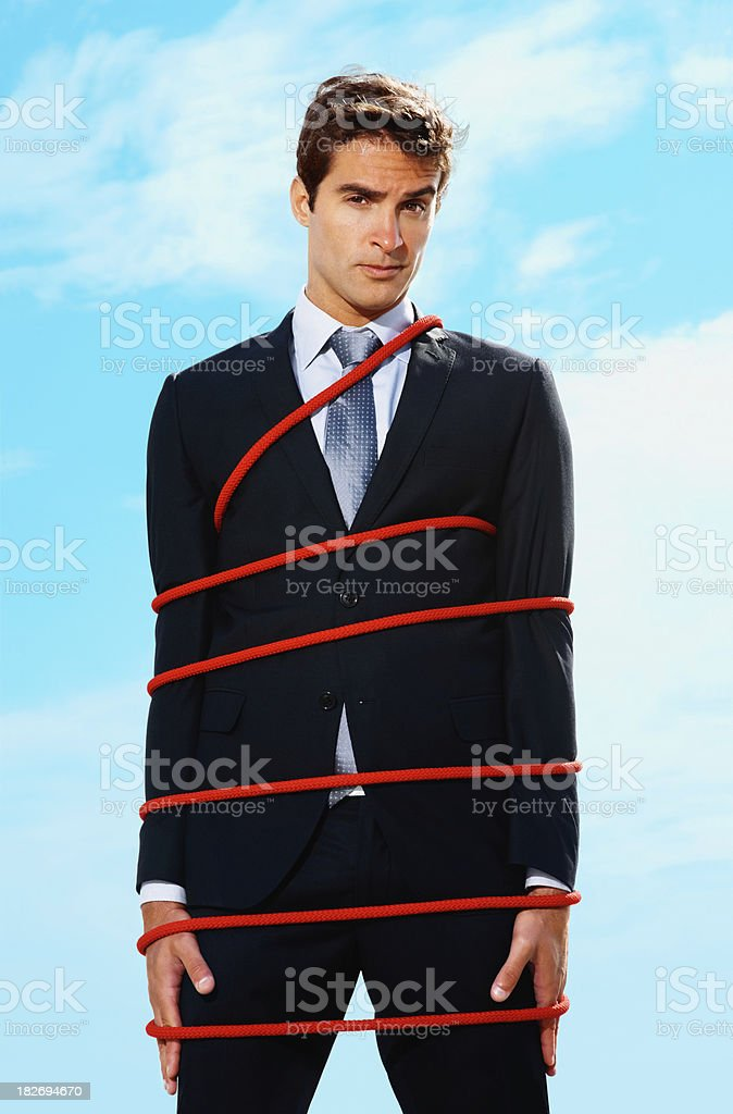 Young business executive tied up with a rope royalty-free stock photo