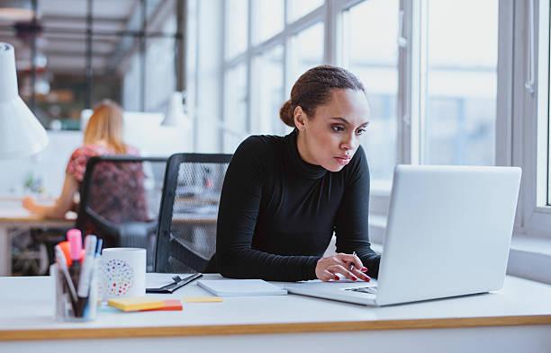 young business executive using laptop - konsantre olma stok fotoğraflar ve resimler