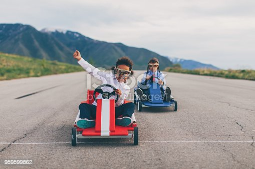 959599892 istock photo Young Business Girl Beats Boy in Car Race 959599862