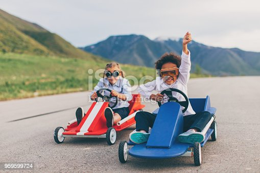 Young business girls dressed in business attire and race goggles in push carts down a rural road in Utah. These business children love racing and competing and working hard for the success of their business. The one business girl gives a raised hand in victory at the finish line.  They both smile for the camera.