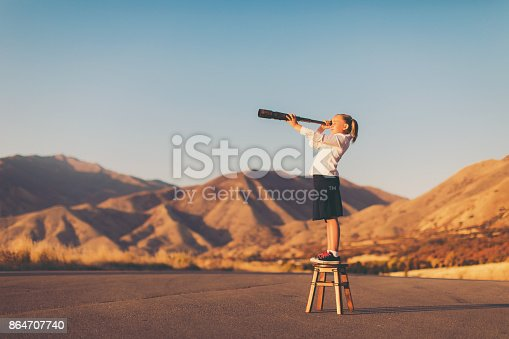 istock Young Business Girl Looks through Telescope 864707740