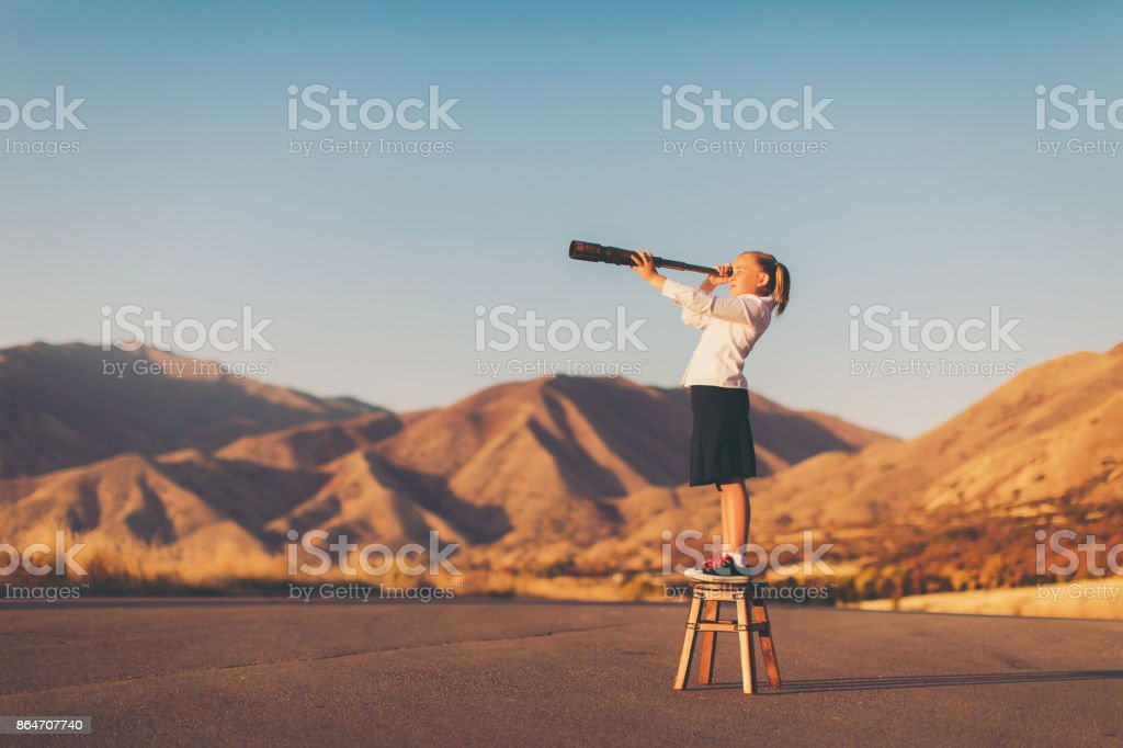 Young Business Girl Looks through Telescope stock photo