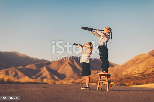 istock Young Business Girl Looks through Telescope 864707762