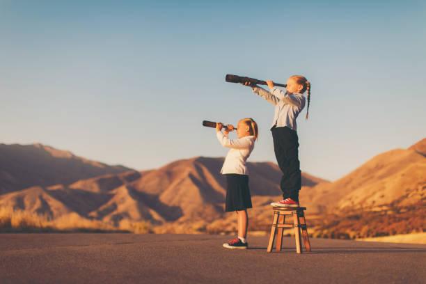 junge mädchen sieht durch teleskop - traum team stock-fotos und bilder