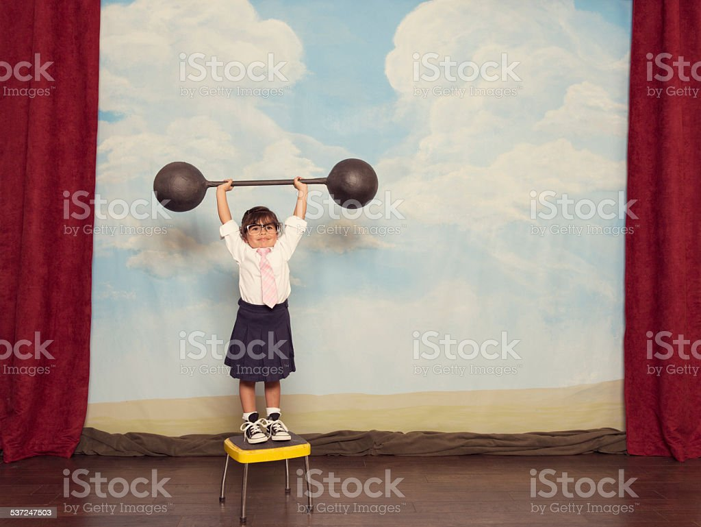 Young Business Girl on Stage Lifting Barbell stock photo