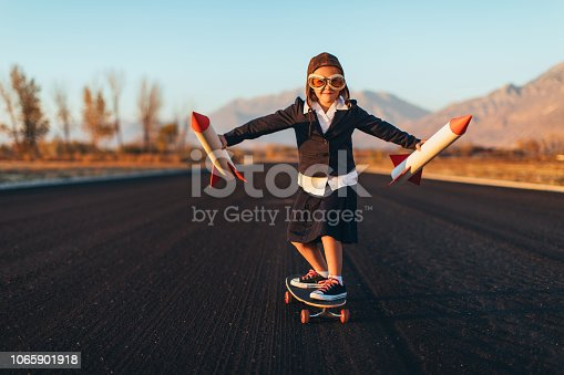 A young business girl dressed in a business attire and aviator glasses, holds rockets while riding a skateboard. She is ready to launch her startup business into the sky. This entrepreneur is eager to make money with her new ideas. Image taken in Utah, USA.