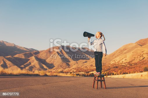 A young girl dressed in business attire stands on a stool in the mountains of Utah yelling through a megaphone. She is ready to advertise for her business and wants you to hear her message.