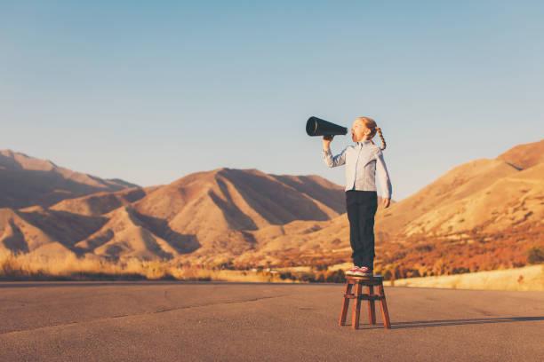 a young business girl uses megaphone - megafono foto e immagini stock