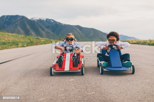 Young business girls dressed in business attire and race goggles race in push carts down a rural road in Utah. These business children love racing and competing and working hard for the success of their business. They speed to the finish line for the win.