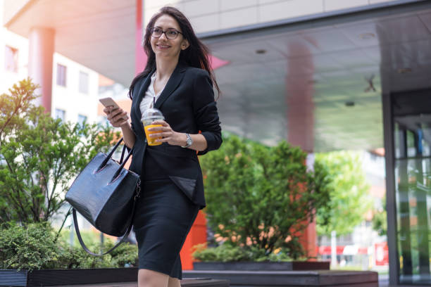 Young business lady texting on the phone and walking in the office park stock photo