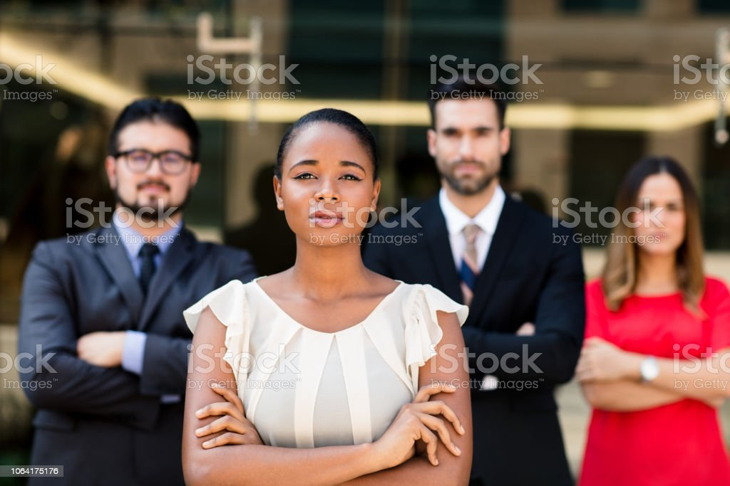 A young executive leader of a multi-ethnic business team posing in...