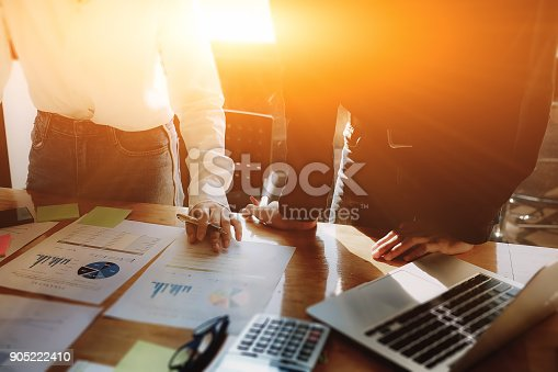 905819004istockphoto young business man and business woman use computer laptop and calculator and stock marketing paper for analyze the company's sales plan for improve sell quality next month at office. 905222410