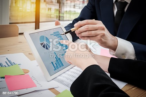 881542122istockphoto young business man and partner using  tablet with graph chart, a 881541790