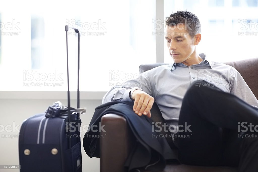 Young business man at the airport lounge checking time royalty-free stock photo