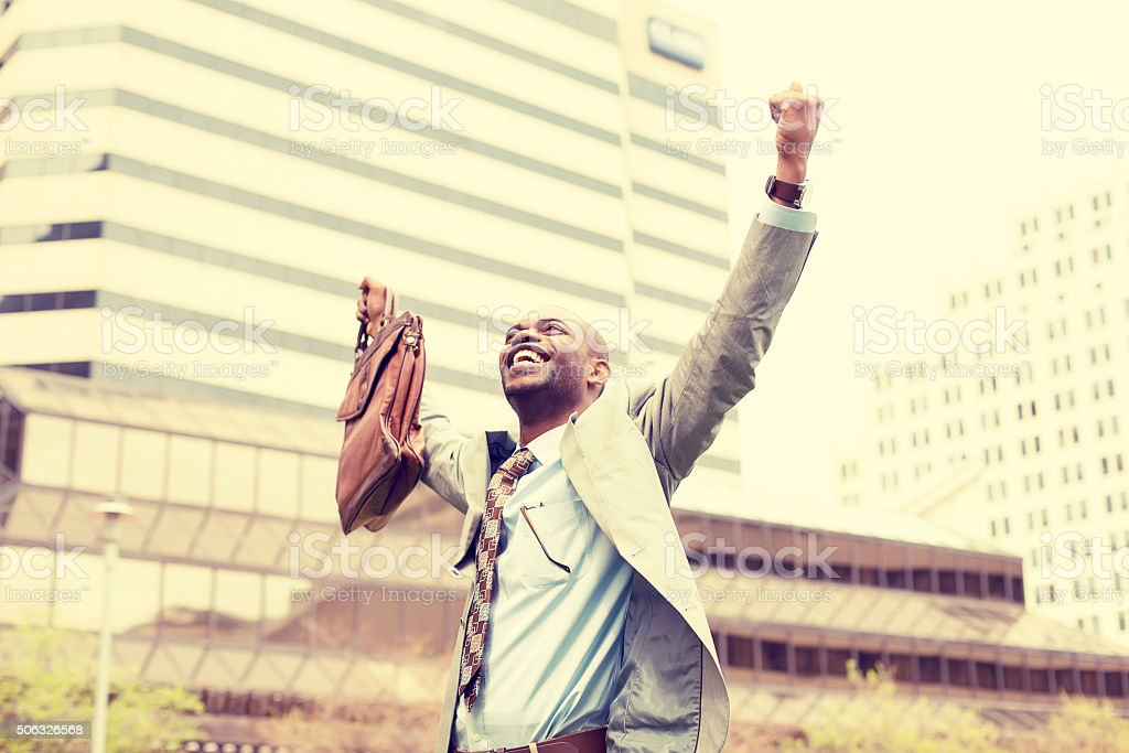 Young business man celebrates freedom success arms raised stock photo