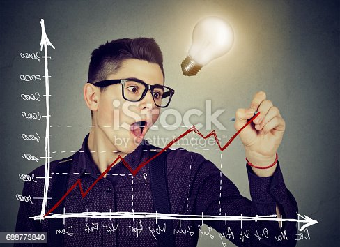 Young business man charting a positive trend graph has bright idea