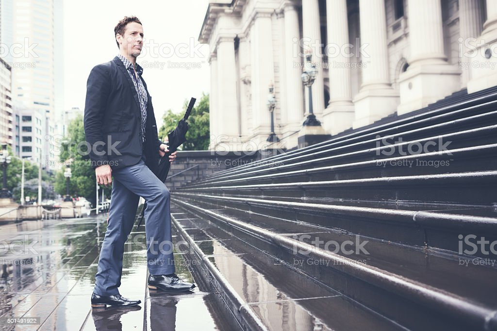 Young business man climbing steps on way to work horizontal stock photo