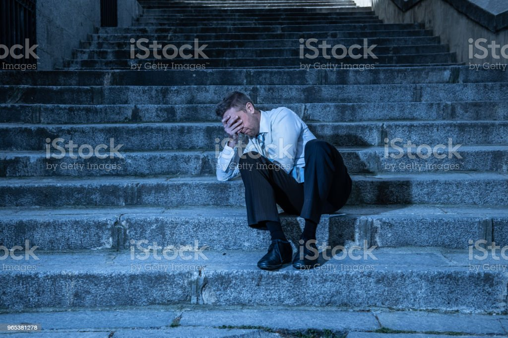 young business man crying abandoned lost in depression sitting on the street stairs suffering emotional pain, sadness in a mental health concept photo royalty-free stock photo