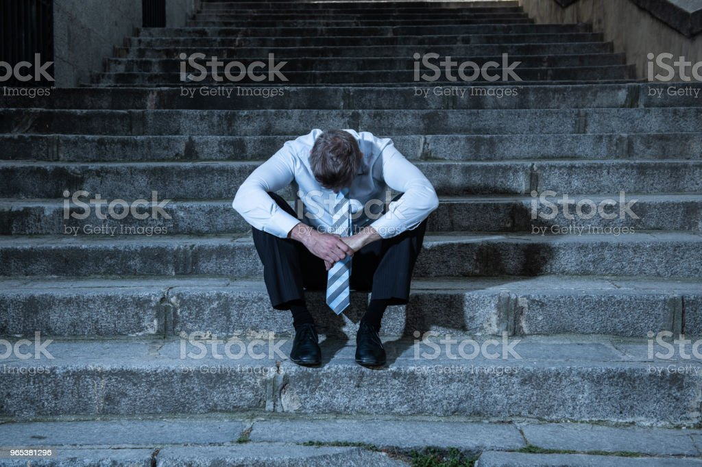 young business man crying abandoned lost in depression sitting on the street stairs suffering emotional pain, sadness in a mental health concept photo zbiór zdjęć royalty-free