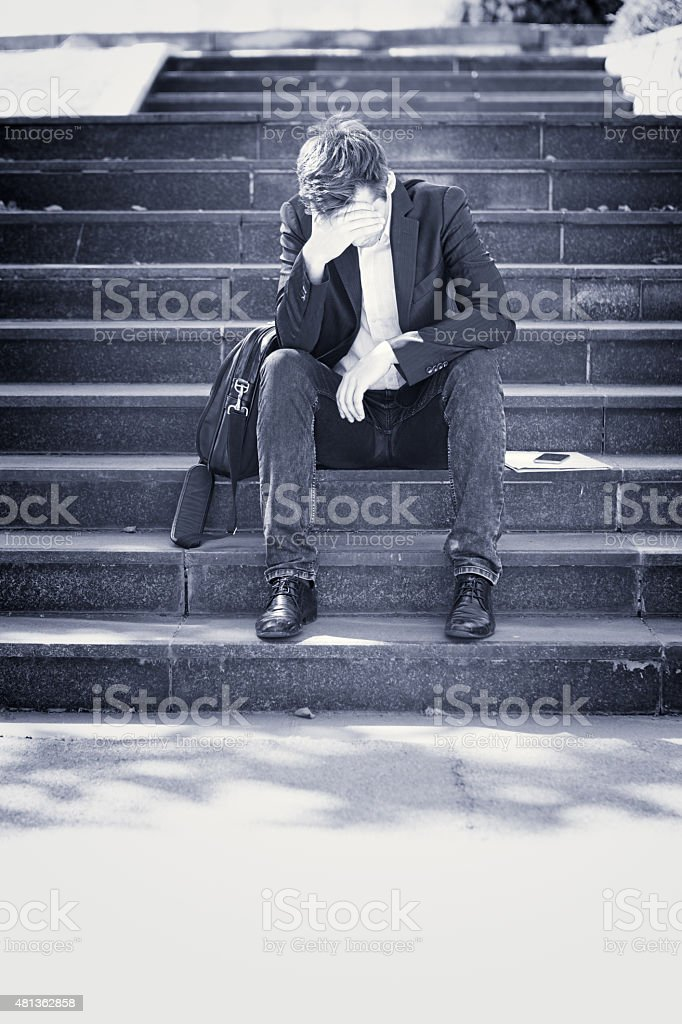 Young business man crying abandoned lost in depression sitting on...