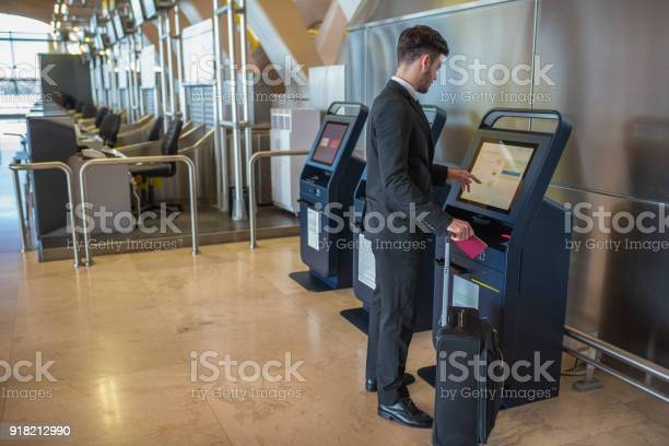 Young business man doing self check in a machine at the airport picture id918212990?b=1&k=6&m=918212990&s=612x612&h=wpsvzk0uwv p75fpbqylp0pr6sakjmyjzzegxvsuc58=