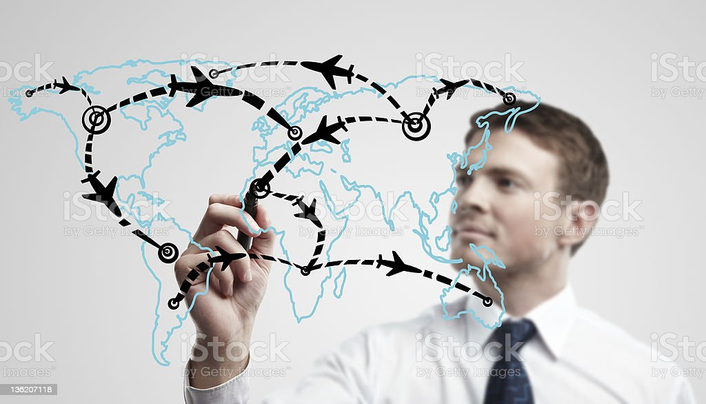 Young business man drawing an airplane routes on world map royalty-free stock photo