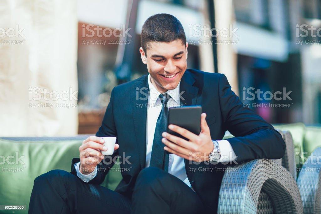 Negócios jovem homem beber café da manhã e usar seu tablet digital. - Foto de stock de Adulto royalty-free