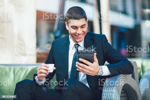 Foto de Negócios Jovem Homem Beber Café Da Manhã E Usar Seu Tablet Digital e mais fotos de stock de Adulto