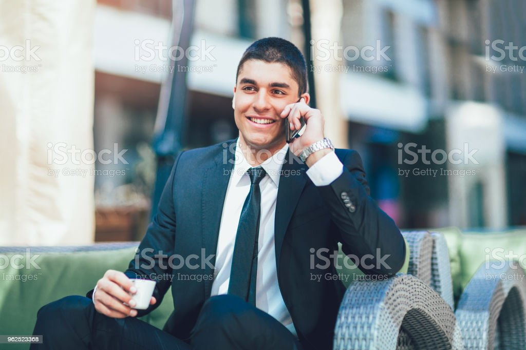 Young business man drinking morning coffee and use his smart phone. - Royalty-free 20-29 Years Stock Photo