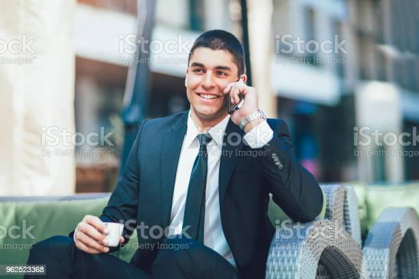 Foto de Negócios Jovem Homem Beber Café Da Manhã E Usar O Seu Telefone Inteligente e mais fotos de stock de 20 Anos