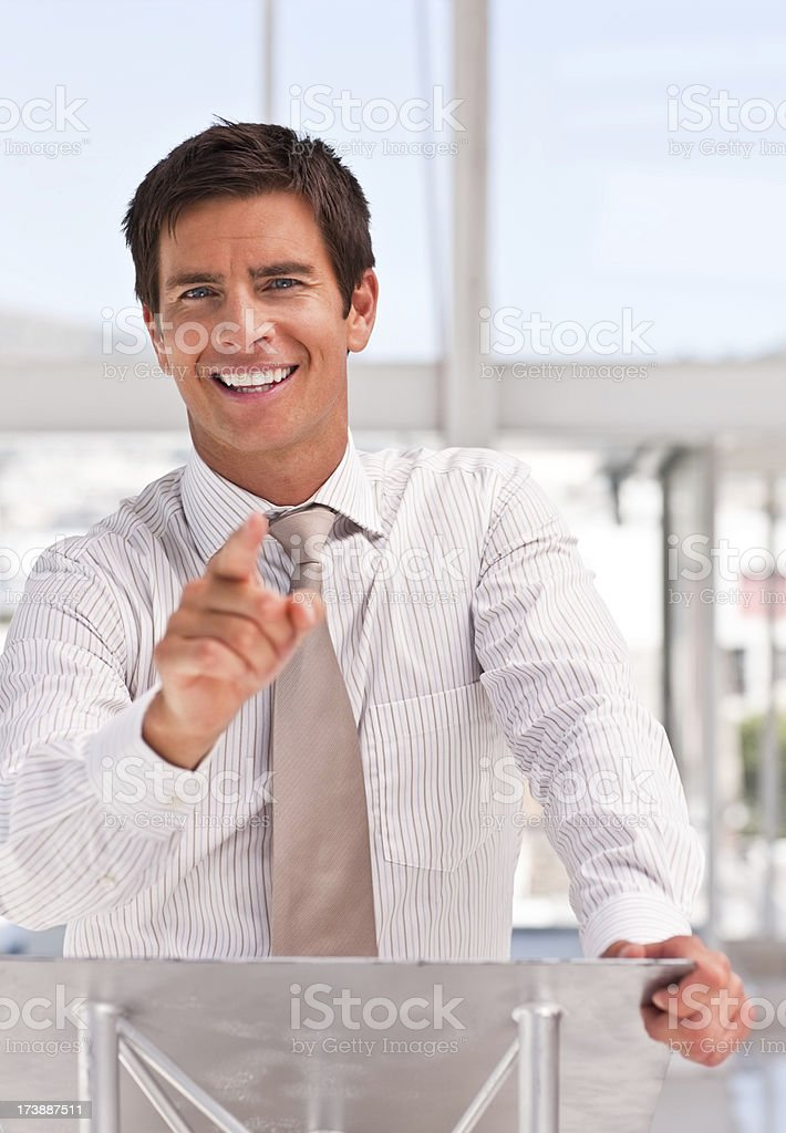 Young business man giving a speech at the podium royalty-free stock photo