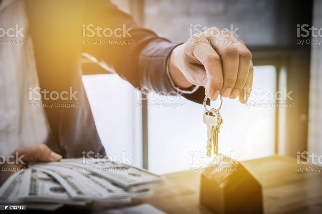 Young business man giving house keys  of customer  and holding dollar us bank at  agency office. agreement concept. stock photo