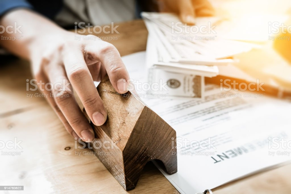 Young business man giving house  of customer  and holding dollar us bank at  agency office. agreement concept. stock photo