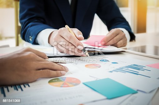 istock Young business man hand holding pen pointing  graph data documen 881541068