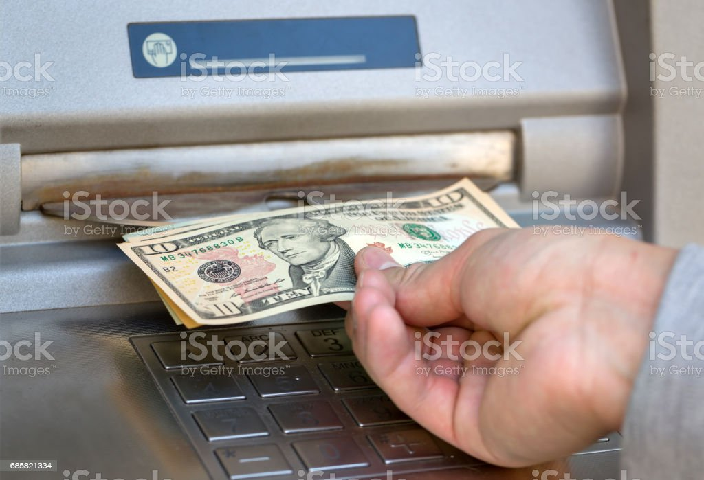 young business man hand show dollar bills in front of atm stock photo