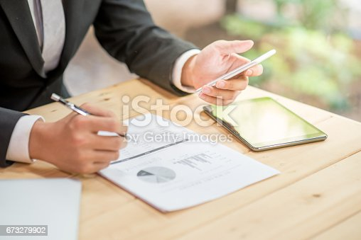 istock young business man in black suit checking summary report and using smartphone 673279902