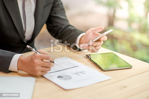 istock young business man in black suit checking summary report and using smartphone 683348880
