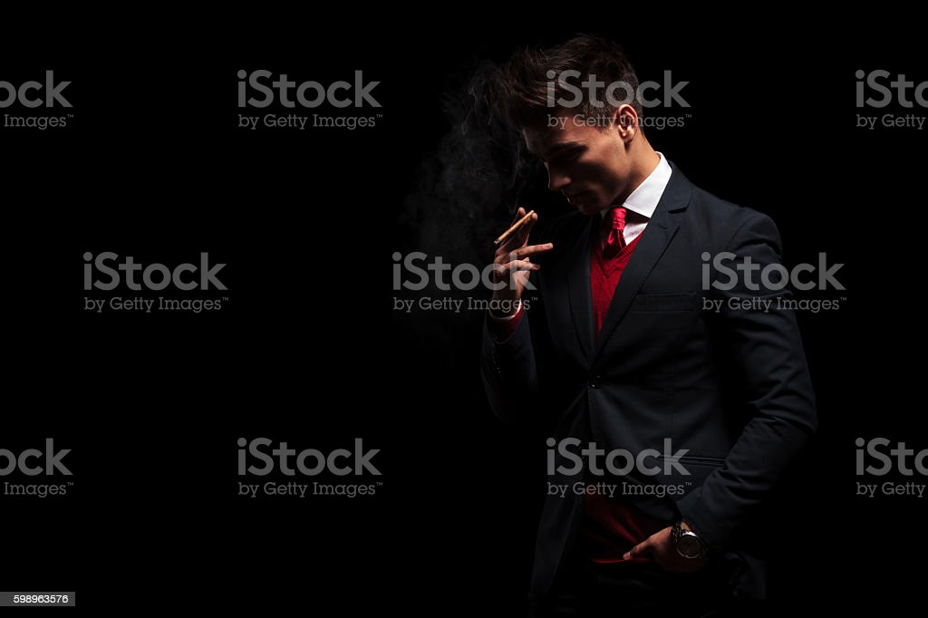 young business man is thinking while smoking his cigarette stock photo