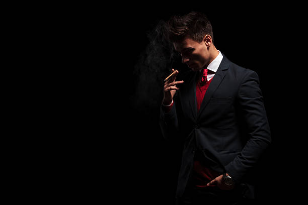 young business man is thinking while smoking his cigarette - guy with cigar stockfoto's en -beelden