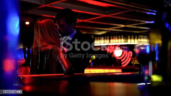 istock Young business man kissing woman in night club, couple of lovers, temptation 1072207490