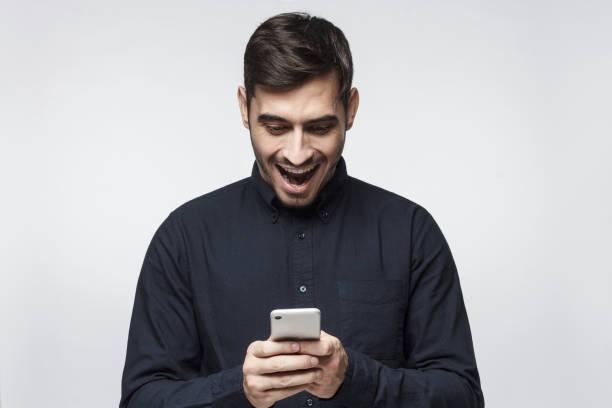 junger geschäftsmann smartphone mit überraschung ausdruck, auf grauem hintergrund isoliert betrachten - die besten apps stock-fotos und bilder