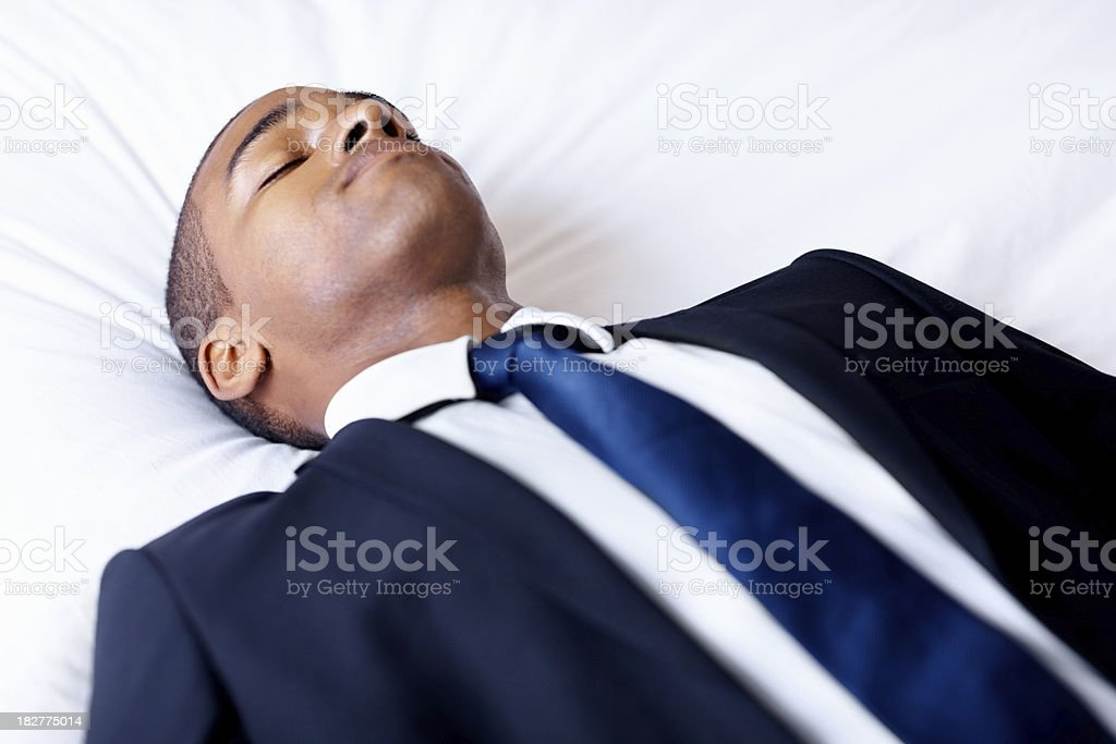 Young business man lying asleep on bed royalty-free stock photo